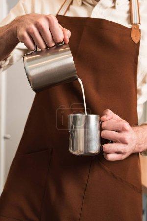 Photo pour Vue recadrée du barista en tablier brun versant du lait dans une cruche en acier - image libre de droit