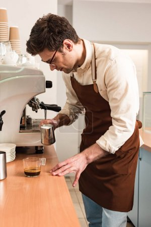 Photo for Barista in glasses and brown apron preparing coffee - Royalty Free Image