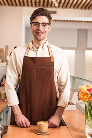 Photo for Laughing barista in glasses and brown apron with cup of coffee - Royalty Free Image