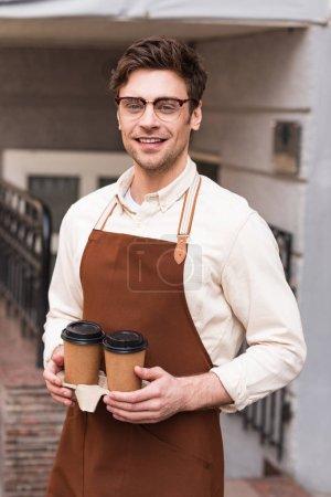 Photo pour Barista souriant dans des lunettes tenant porte-gobelet à emporter avec café - image libre de droit