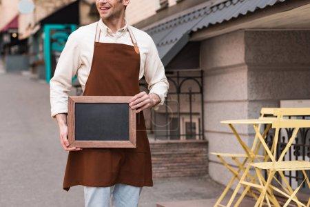 Photo pour Vue cultivée de barista de sourire dans le tablier brun retenant le menu de tableau sur la rue - image libre de droit