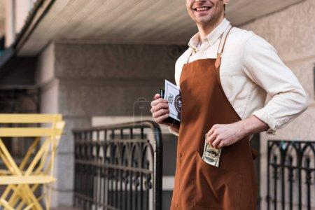 Vista parcial de barista en delantal marrón poniendo dinero en el bolsillo