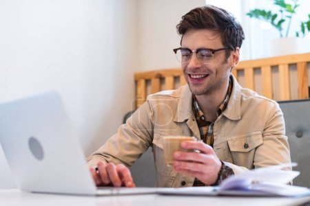 Smiling freelancer in glasses holding cup of coffee and typing on laptop keyboard