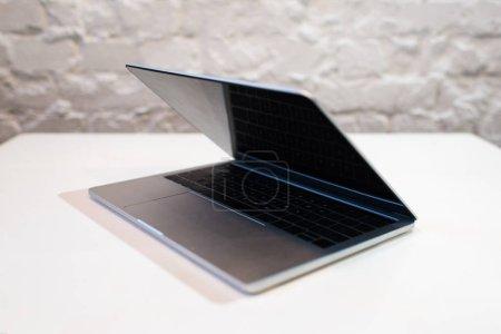 Photo pour Ordinateur portatif moderne avec l'écran blanc sur la table blanche dans le café - image libre de droit
