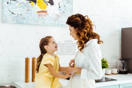 Photo pour Mère heureuse riant avec le descendant ensemble dans la cuisine - image libre de droit
