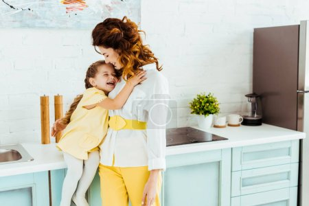 Photo for Happy mother laughing and hugging with daughter together in kitchen - Royalty Free Image