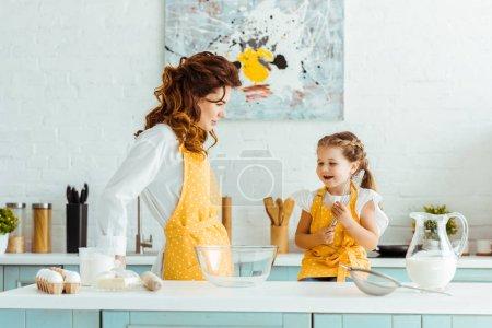 Photo pour Mère à pois tablier jaune regardant fille excitée dans la cuisine - image libre de droit