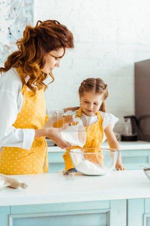 Photo pour Mère à pois tablier jaune aidant fille attentive ajoutant de la farine au bol - image libre de droit
