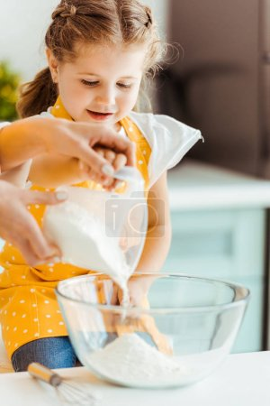 Photo for Selective focus of woman adding flour to bowl near excited daughter in kitchen - Royalty Free Image