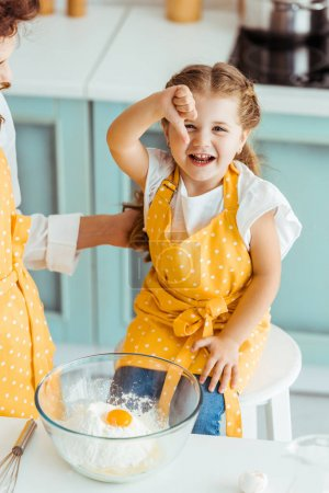 Photo for Mother touching daughter in apron near bowl with flour and smashed egg while excited child showing thumb down - Royalty Free Image