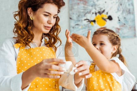 selective focus of mother holding eggshell while daughter gesturing in kitchen