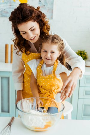 Photo for Happy mother with excited daughter standing together near bowl with eggs and flour in kitchen - Royalty Free Image