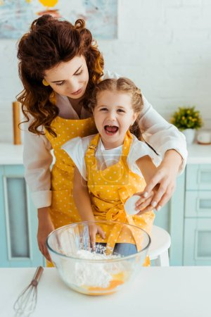 Photo for Mother and excited daughter smashing egg together into bowl with flour in kitchen - Royalty Free Image