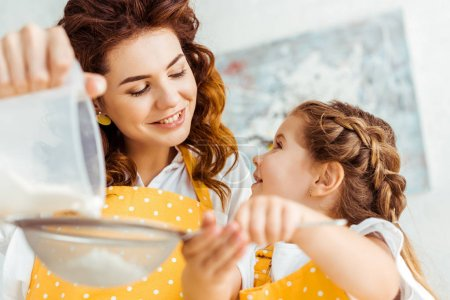 Photo for Selective focus of smiling mother and daughter sieving flour together - Royalty Free Image