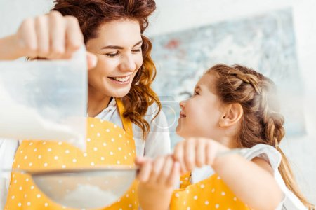 Photo for Selective focus of happy mother and daughter sieving flour together - Royalty Free Image