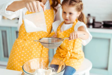 selective focus of mother and daughter sieving flour together into bowl