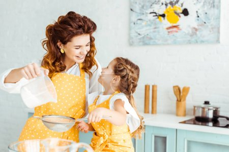 Photo for Selective focus of happy mother and daughter sieving flour together in kitchen - Royalty Free Image
