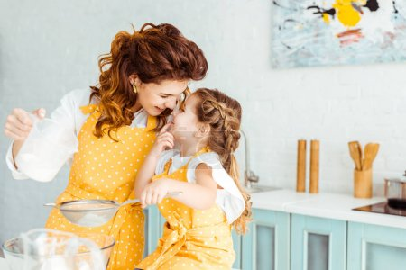 Photo for Selective focus of cute mother and daughter sieving flour together in kitchen - Royalty Free Image