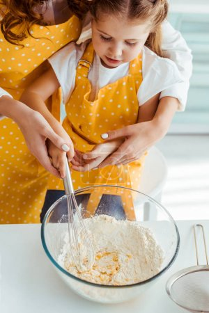 Photo for Mother and daughter in aprons mixing flour and eggs with balloon whisk in bowl - Royalty Free Image