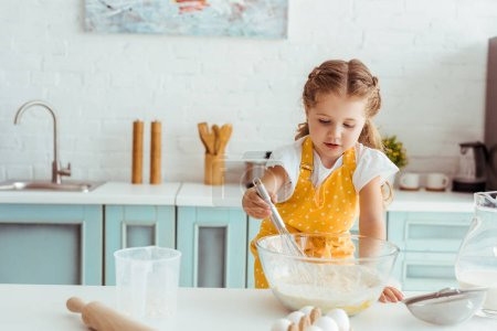 Photo for Concentrated kid in yellow polka dot apron cooking dough in kitchen - Royalty Free Image