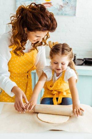 Foto de Madre feliz ayudando a la hija de desplegar la masa en papel de pergamino para hornear - Imagen libre de derechos
