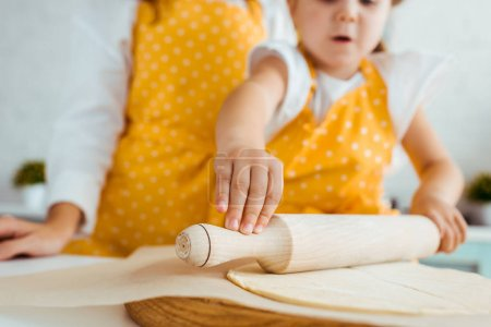 Photo for Cropped view of mother and excited daughter rolling out dough with wooden rolling pin on baking parchment paper - Royalty Free Image