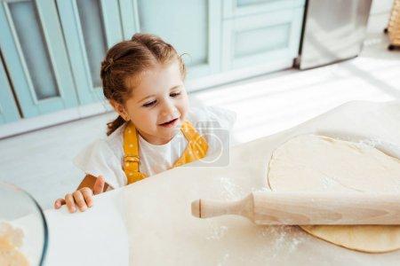 Foto de Niño excitado mirando la masa con rodillo de madera en papel de pergamino de hornear - Imagen libre de derechos