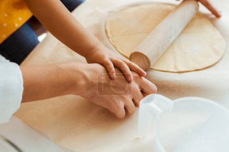 Photo for Cropped view of mother and daughter rolling out dough with wooden rolling pin together - Royalty Free Image