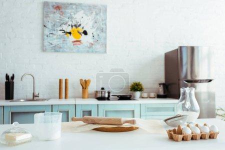 Foto de Interior of light modern kitchen with bakery ingredients on table - Imagen libre de derechos