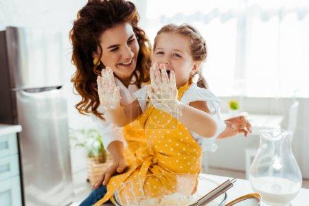 Foto de Madre sonriente mirando a la hija riendo con las manos sucias en la masa - Imagen libre de derechos