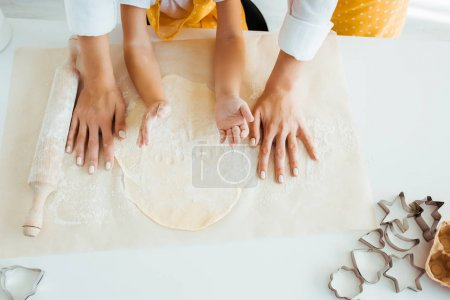 Photo for Top view of mother and daughter with dough, rolling pin and dough molds on table - Royalty Free Image