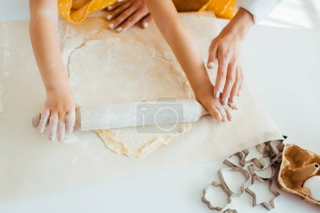Photo for Top view of mother and daughter rolling out dough near dough molds on table - Royalty Free Image