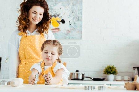 Photo pour Mère heureuse en tablier à pois jaunes regardant fille tenant des moules à pâte dans la cuisine - image libre de droit