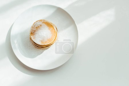 Photo for Top view of tasty pancakes with sugar powder on plate - Royalty Free Image
