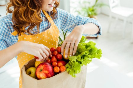 Photo for Cropped view of happy woman near paper bag with ripe fruits and vegetables on kitchen table - Royalty Free Image