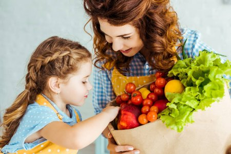 Photo for Happy mother showing daughter paper bag with ripe fruits and vegetables - Royalty Free Image