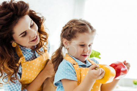 Photo for Happy mother looking at daughter holding red and yellow bell peppers - Royalty Free Image