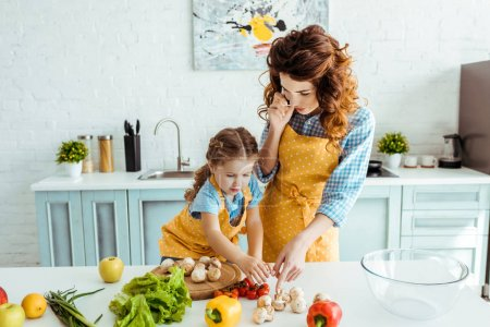 Photo for Mother and daughter in polka dot aprons standing near table with raw fruits and vegetables - Royalty Free Image