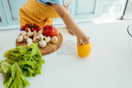 Photo for Cropped view of child in polka dot apron holding yellow bell pepper on table with vegetables and chopping board - Royalty Free Image