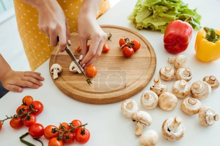 Photo for Cropped view of woman in polka dot apron cutting mushrooms and cherry tomatoes on chopping board near daughter - Royalty Free Image