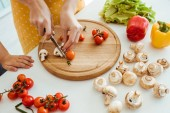 "Постер, картина, фотообои ""cropped view of woman in polka dot apron cutting mushrooms and cherry tomatoes on chopping board near daughter"""