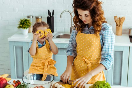 Photo for Cute daughter holding bell pepper slices in front of eyes while mother cutting vegetables - Royalty Free Image