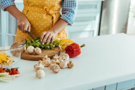 Photo for Partial view of woman cutting lettuce on wooden chopping board - Royalty Free Image