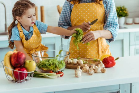 Photo for Mother in polka dot yellow apron giving daughter sliced lettuce - Royalty Free Image