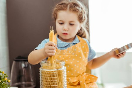 Photo for Selective focus of child in polka dot yellow apron holding raw spaghetti - Royalty Free Image