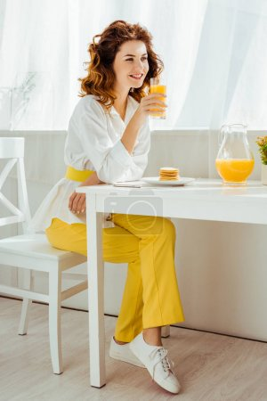 beautiful happy woman sitting at table and drinking orange juice while having breakfast