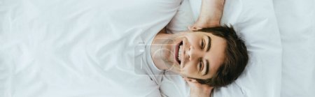 Photo for Panoramic shot of happy man looking at camera while lying on bed - Royalty Free Image