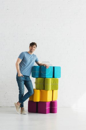 Photo for Cheerful man standing and smiling near colorful poufs near brick wall - Royalty Free Image