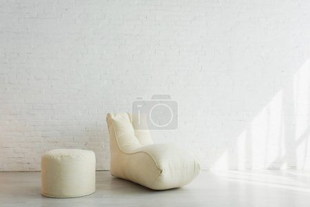 Photo for Bean bag chair and pouf near white brick wall in modern home - Royalty Free Image