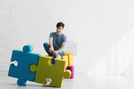 Foto de Hombre alegre mirando piezas de rompecabezas azules y verdes mientras se sienta cerca de la pared de ladrillo - Imagen libre de derechos